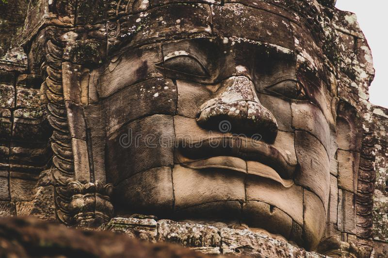 estátua principal de pedra Líquene-coberta em Angkor Wat, Siem Reap, Camboja, Indochina, Ásia - cara sobre na cor foto de stock