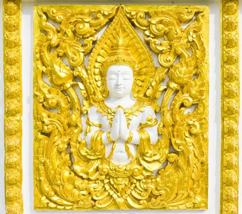 Estátua sobre a religião na parede, templo tailandês foto de stock royalty free