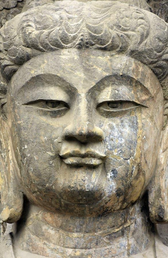 Estátua velha de pedra de uma Buda Ascendente próximo da cara, stat da Buda da cara fotografia de stock