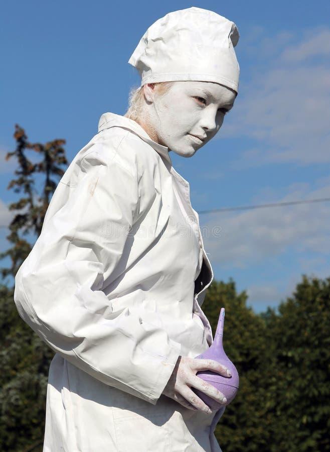 Estátua viva de um doutor com enema em suas mãos fotografia de stock