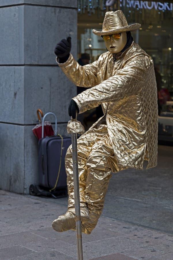 Estátua viva de um homem assentado em uma cadeira invisível imagens de stock royalty free