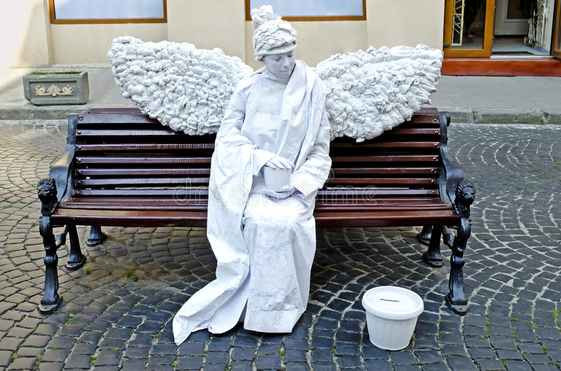 Estátua viva - um anjo branco que senta-se em um banco fotos de stock royalty free