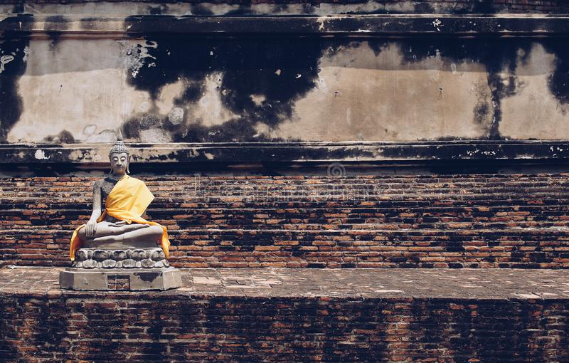 Estátuas antigas da Buda colocadas em paredes de tijolo em templos tailandeses imagens de stock