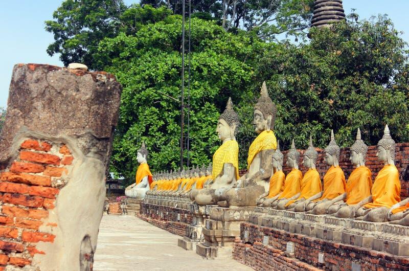 Estátuas antigas da Buda na fileira que medita, no templo antigo de Wat Yai Chaimongkol em Ayutthaya, Tailândia imagem de stock