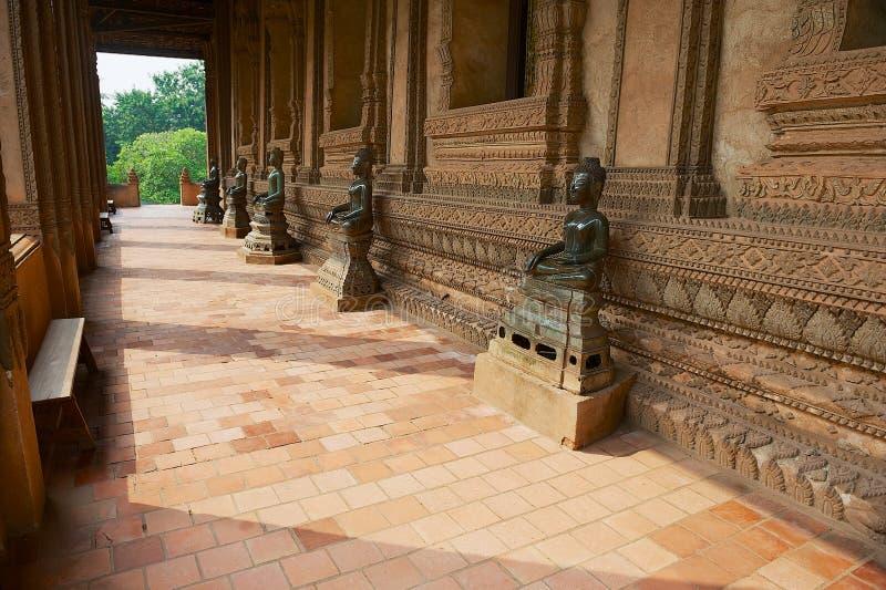 Estátuas antigas da Buda situadas ao longo da parede exterior da construção do museu de Hor Phra Keo em Vientiane, Laos imagem de stock