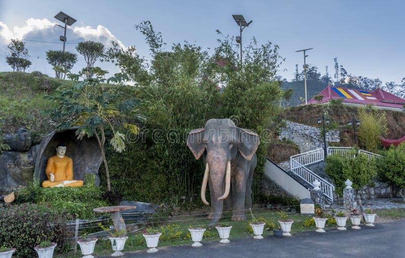 Estátuas da Buda e do elefante na jarda do templo budista fotos de stock