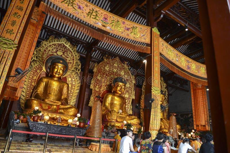 Estátuas de três Buddhas no templo imagem de stock