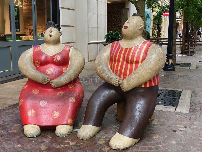 Estátuas de um par que aprecia o assento exterior em Hong Kong imagens de stock royalty free