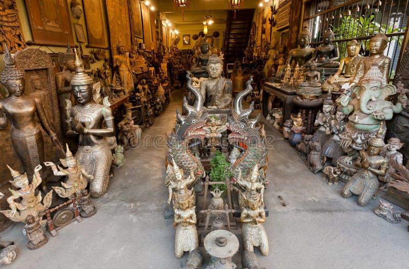 Estátuas do vintage da Buda e de lembranças de madeira tradicionais na loja antiga da cidade tailandesa imagens de stock