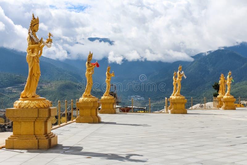 Estátuas douradas de deusas budistas no monte superior no parque natural de Kuensel Phodrang, Thimphu, Butão fotografia de stock royalty free
