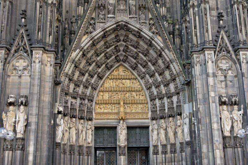 Estátuas e pedra que cinzelam acima da entrada da catedral católica da água de Colônia fotografia de stock