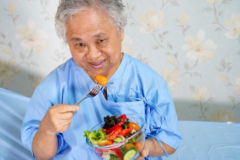 Est?tuas tailandesas do rei em RajabhaktiparkAsian superior ou no paciente idoso da mulher da senhora idosa que come o alimento s fotos de stock royalty free