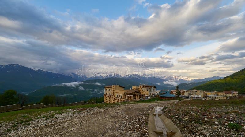 Estância de esqui na primavera contra o contexto de montanhas nevados em um dia nebuloso fotografia de stock royalty free