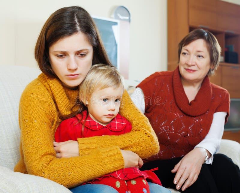 Esté en conflicto entre la mujer triste con el bebé y la madre madura fotografía de archivo libre de regalías