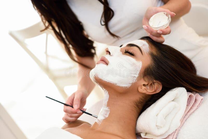 Estética que aplica una máscara a la cara de una mujer hermosa imágenes de archivo libres de regalías