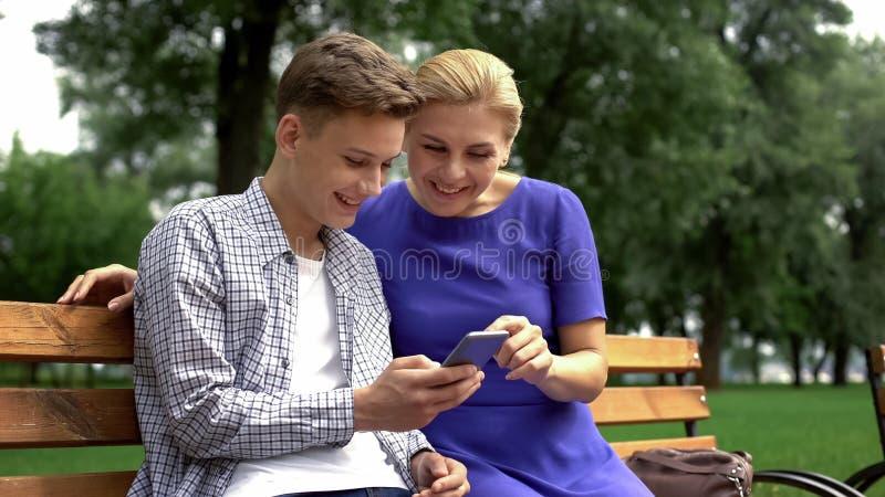 Estórias boas de leitura da mamã e do filho no smartphone, sentando-se no banco no parque, divertimento fotos de stock