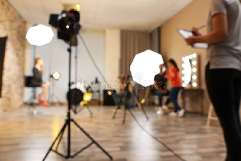 Estúdio borrado da foto com equipamento e os trabalhadores profissionais fotografia de stock royalty free