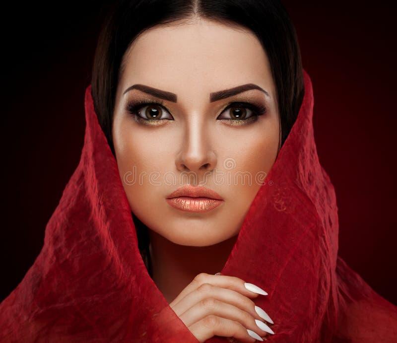 Estúdio, cara, olhos marrons, xaile vermelho, fundo vermelho foto de stock royalty free