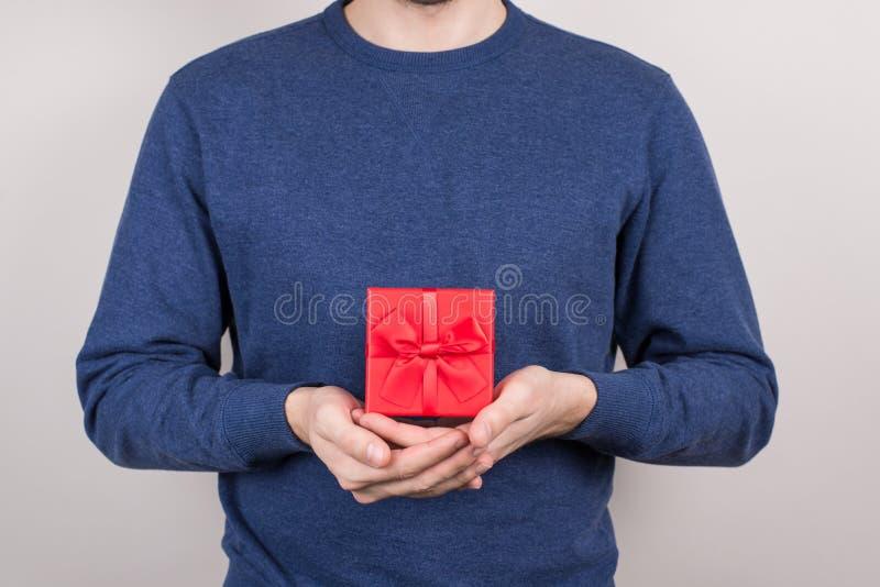 Estúdio colhido da foto do close-up disparado da boa pessoa otimista positiva contente alegre que mostra o recipiente quadrado ag imagens de stock
