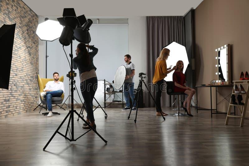 Estúdio da foto com equipamento e a equipe profissionais imagem de stock