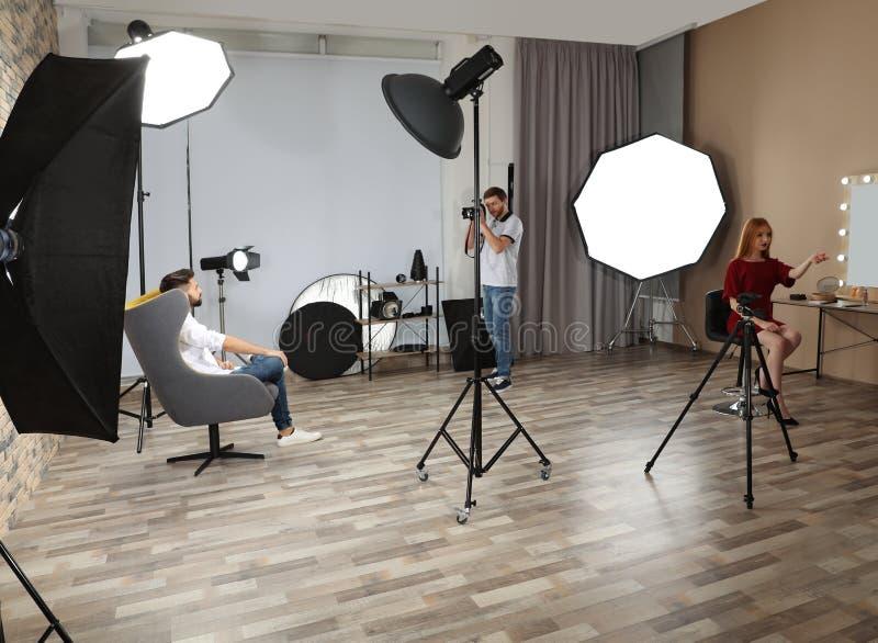 Estúdio da foto com equipamento e os trabalhadores profissionais imagem de stock