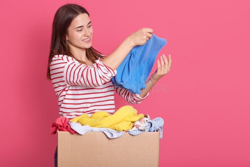 Estúdio de jovem voluntário segurando roupas nas mãos, examinando coisas para uso secundário, senhora se posando isolada sobre ro imagens de stock royalty free