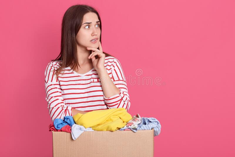 Estúdio de mulher penosa com cabelo escuro, mantendo o dedo na bochecha, olhando de lado, parece atencioso, segurando roupas doad fotografia de stock