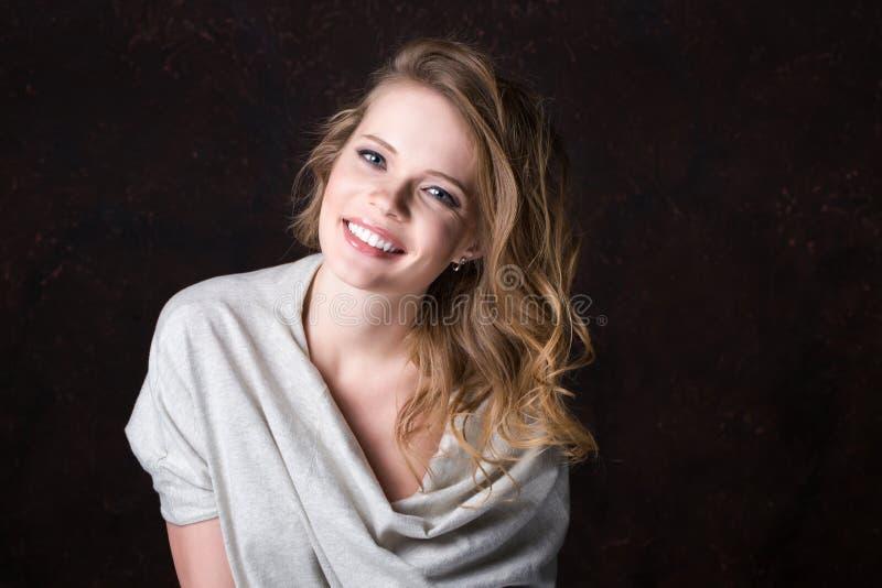 Estúdio de sorriso novo bonito da mulher em um fundo escuro fotos de stock royalty free