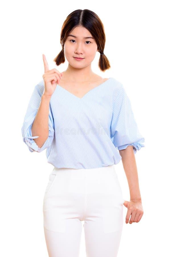 Estúdio disparado da mulher asiática bonita nova que aponta o dedo acima fotografia de stock royalty free
