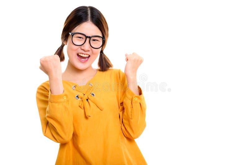 Estúdio disparado da mulher asiática feliz nova que cheering com ambos os braços r foto de stock royalty free