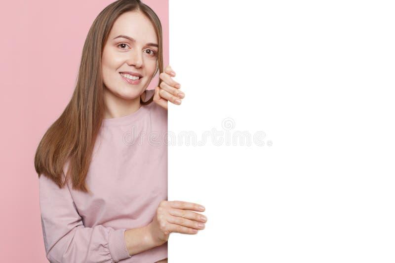 Estúdio disparado da mulher parecendo jovem agradável alegre na roupa ocasional, do lugar das posses espaço vazio, branco para su foto de stock royalty free
