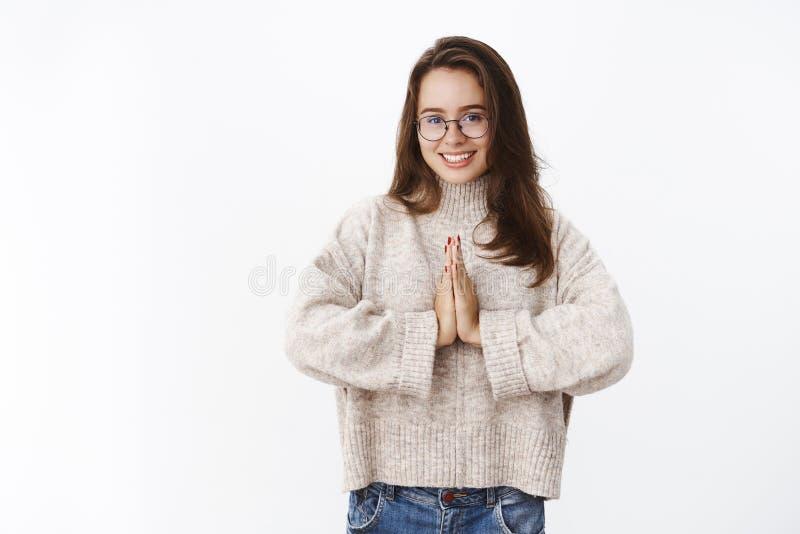 Estúdio disparado da mulher 20s nova bonito e feminino nos vidros e na camiseta que mantêm as palmas unidas perto do corpo no nam imagem de stock royalty free