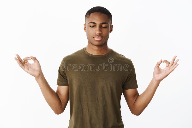 Estúdio disparado da posição afro-americano nova calma e calma do desportista na pose dos lótus que procura o nirvana e a paciênc imagens de stock