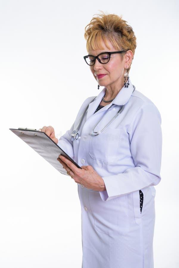 Estúdio disparado da posição asiática superior do doutor da mulher ao ler imagens de stock