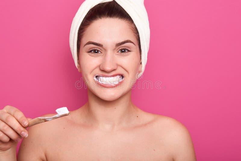 Estúdio disparado de smies bonitos da jovem mulher amplamente, escovando seus dentes e olhando a câmera com a expressão facial fe imagem de stock royalty free