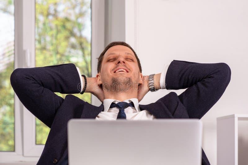 Estúdio disparado de um homem de sorriso novo que senta-se com suas mãos atrás de sua cabeça que trabalha em seu portátil imagem de stock royalty free