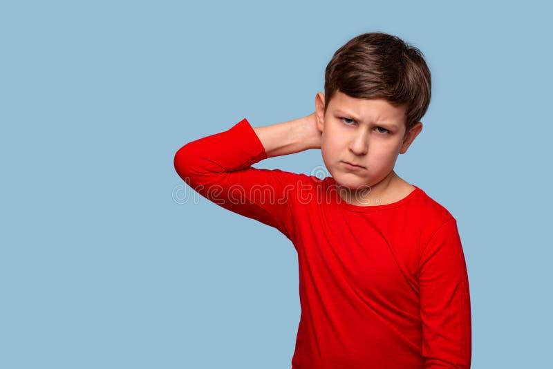 Estúdio disparado de um menino sério que pensa sobre algo que risca sua cabeça, isolado no azul com espaço da cópia foto de stock