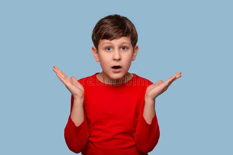Estúdio disparado de um menino sério que quer saber algo que espalha seus braços ao lado, isolado no azul com espaço da cópia foto de stock royalty free