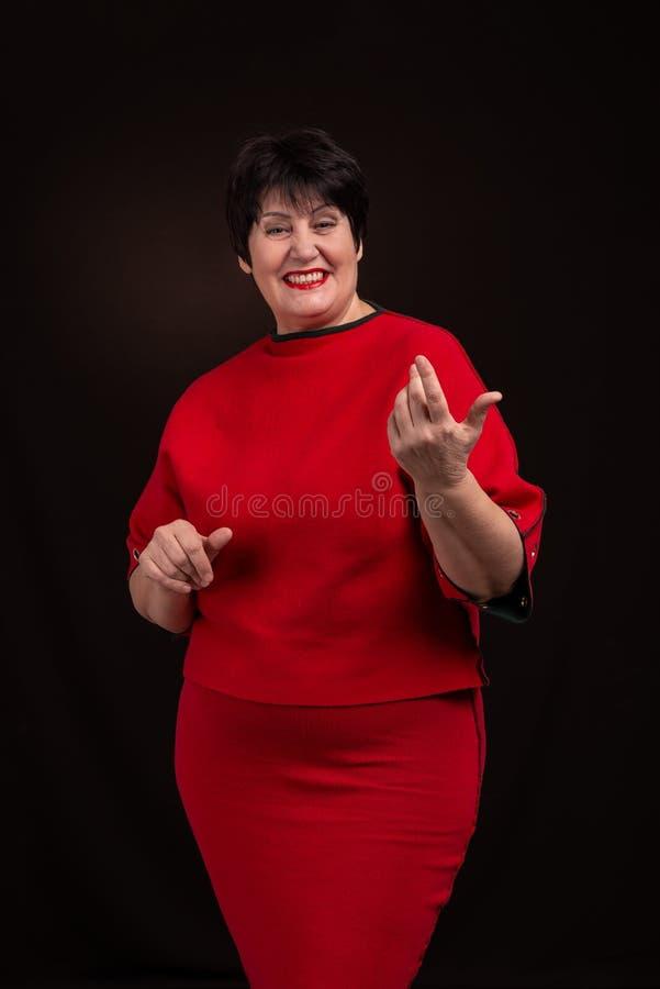 Estúdio disparado de uma mulher de sorriso adulta superior que veste um vestido vermelho em um fundo escuro Está sorrindo alegrem imagens de stock