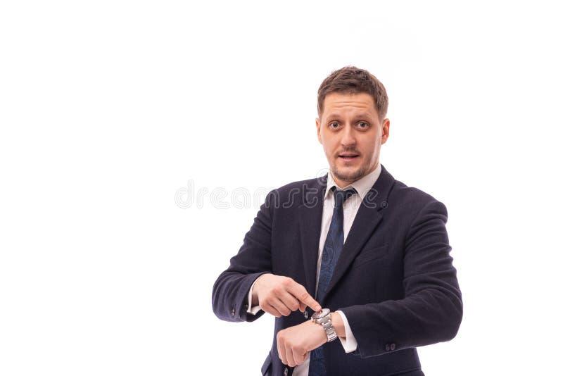 Estúdio disparado de vestir novo do homem de negócios escuro - pontos azuis do terno a cronometrar em um relógio de pulso que rec fotografia de stock