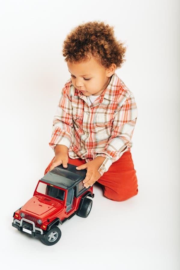 Estúdio disparado do bebê africano adorável do bebê de um ano que joga com carro fotos de stock royalty free