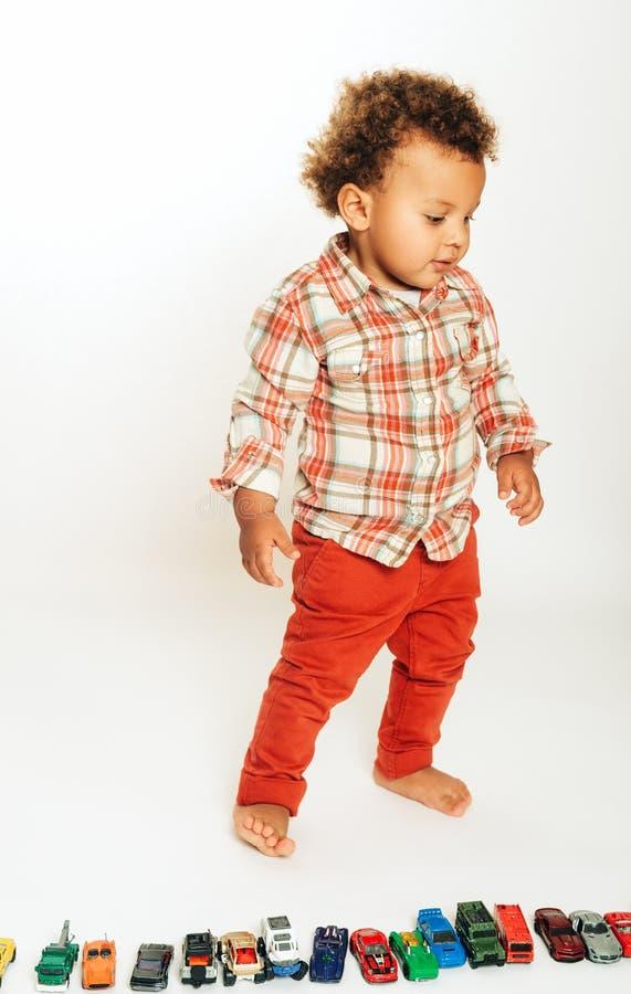Estúdio disparado do bebê africano adorável do bebê de um ano que joga com carros coloridos imagens de stock royalty free
