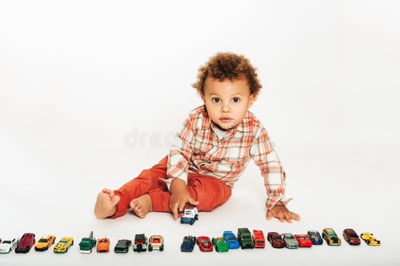 Estúdio disparado do bebê africano adorável do bebê de um ano que joga com carros coloridos fotografia de stock