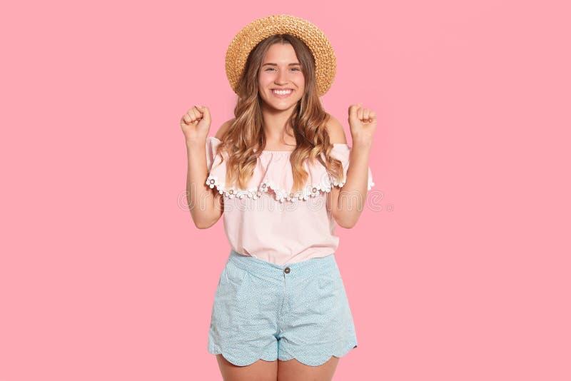 Estúdio disparado do chapéu de palha vestindo fêmea encantador alegre, da blusa leve e do short, levantando suas mãos, estando em fotografia de stock royalty free