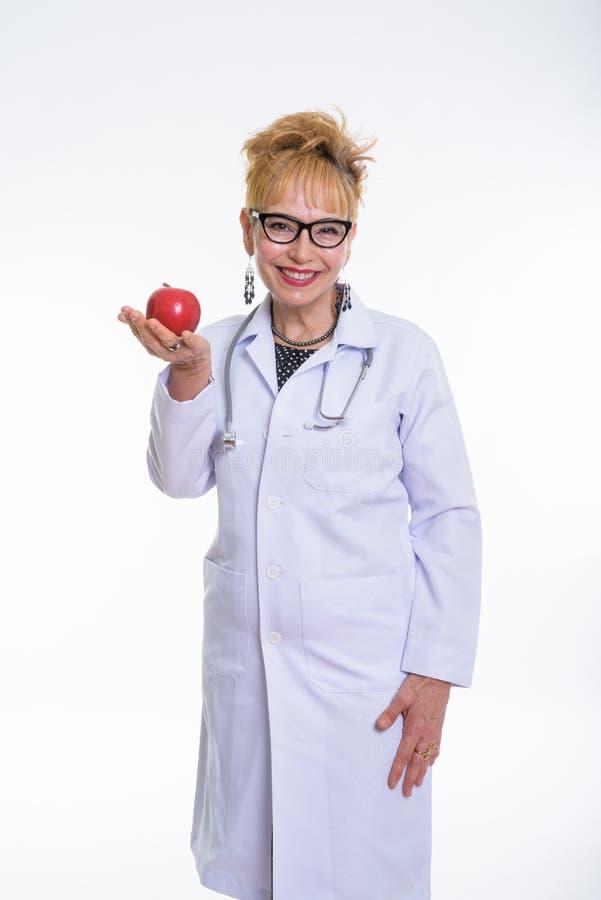 Estúdio disparado do doutor asiático superior feliz da mulher que sorri quando HOL imagem de stock royalty free