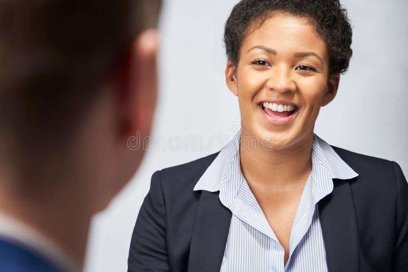 Estúdio disparado do emprego de Interviewing Businessman For da mulher de negócios contra o fundo branco imagem de stock royalty free