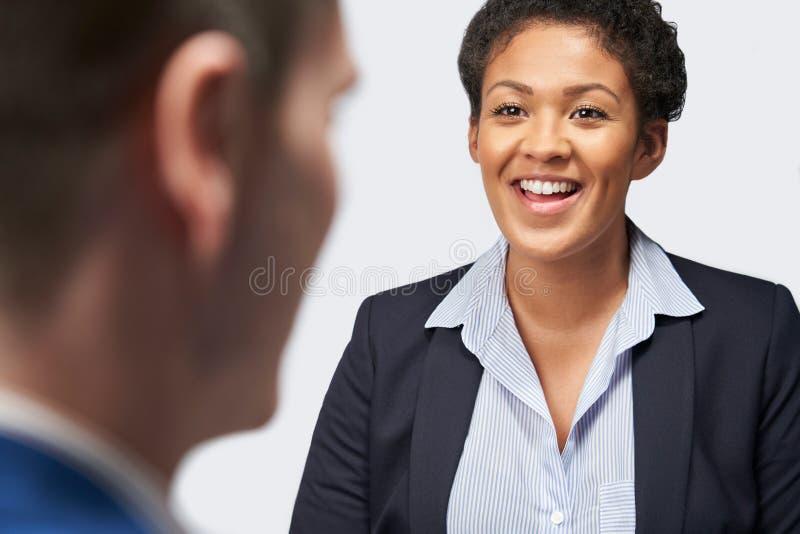 Estúdio disparado do emprego de Interviewing Businessman For da mulher de negócios contra o fundo branco foto de stock royalty free