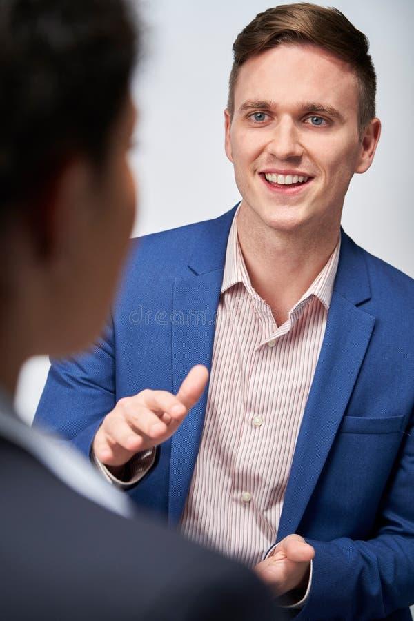 Estúdio disparado do emprego de Interviewing Businesswoman For do homem de negócios contra o fundo branco imagens de stock royalty free