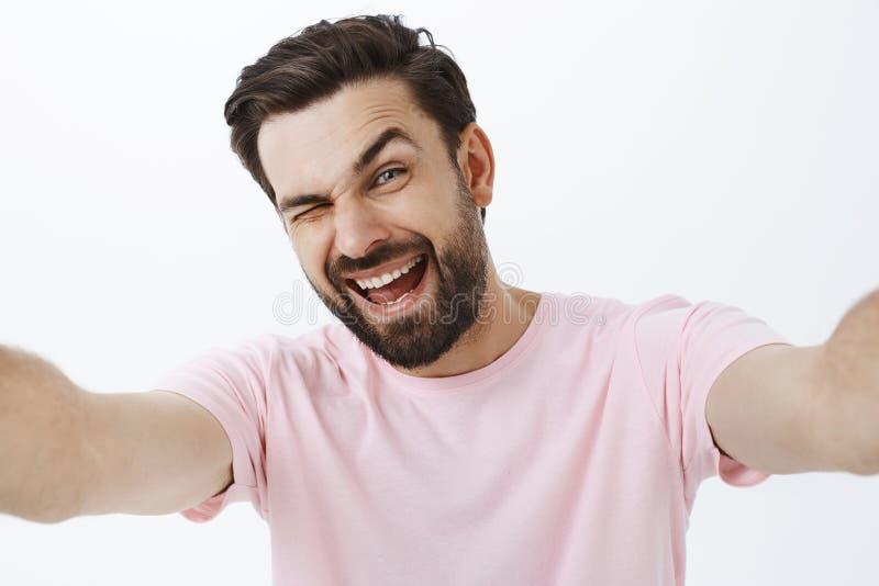 Estúdio disparado do homem macho considerável feliz e entusiástico carismático com barba e penteado escuro que pisc e que sorri imagens de stock