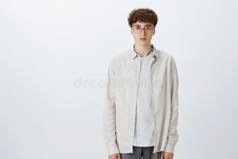 Estúdio disparado do menino europeu considerável e à moda impassível indiferente do moderno nos vidros com posição encaracolado d fotografia de stock